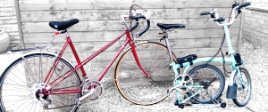 Raleigh Stratos and Brompton bicycles, propped up against the shed
